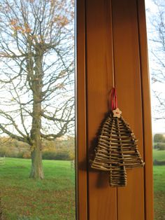 Plain and simple Christmas tree shaped hanging decoration made of woven natural willow with a wooden star button and a raffia loop which can...