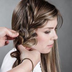 Zum Abschluss wird der Zopf aufgelockert. Dafür die Partie jeweils am Haargummi festhalten und gleichzeitig das Haar erst links und dann rechts in die Breite ziehen. Das sorgt optisch sofort für...