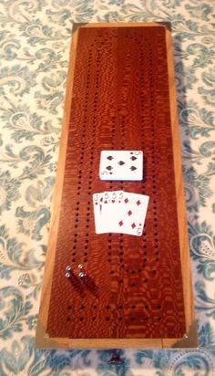 My latest cribbage board made of oak and leopard wood.  Has a drawer for holding cards and pegs.