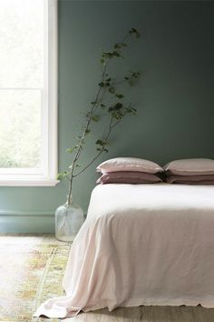 Minimalist bedroom with forest green walls, a small plant, and pink linen bedding