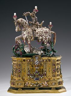 Statuette of St George  (gold, enamel, silver-gilt, diamonds, rubies,  emeralds, opals, agate, chalcedony, rock crystal and other precious stones, pearls;  height 50 cm); Munich, 1586/97 The statuette was made to house a relic of St George that Archbishop Ernst of Cologne sent in 1586 to his brother Duke Wilhelm V of Bavaria. The bearded face of the saint behind the movable visor is carved from boxwood and resembles that of the man who commissioned the statuette, Duke Wilhelm V