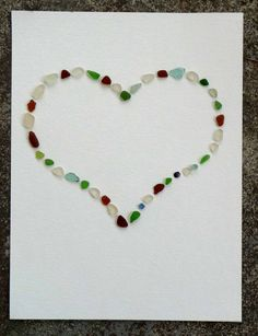 sea glass art - i'd like to do this with all blue/green glass and completely fill the space outside the heart. frame in a deep frame or memory box (with shells on bottom?)