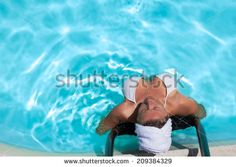 Middle aged Caucasian woman relaxing in blue transparent water at spa. - stock photo