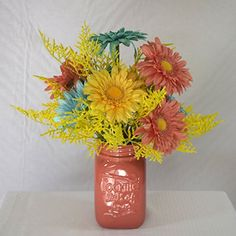"Darling Gerbera Daisies in Mason Jar. You can enjoy a bouquet of mixed color Gerbera daisies and accent fillers. All in a quart sized Mason type glass jar. The jar has ""Cooking Lots of Love"" on one side. Dimensions: D-14"", W-14"", H-18""."