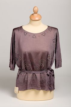 Blouse ca 1922  A steel grey rayon stockinette blouse beaded in metallic grey, copper and pale green round neck, in lengths down bust and at the hem in swirling pattern.