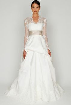Bliss by Monique Lhuillier 1218:  Sabrina neckline bodice with illusion long lace sleeves, natural waist, cummerbund and hand tufted skirt with lace border.
