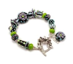 What Goes Around is my latest bracelet featuring a funky and eclectic mix of my own handmade lampwork beads in fun shapes and colors that are out of the ordinary. Jet black encased in crystal clear, with purple, kiwi, and turquoise. Polka dots, flowers, and stripes, oh my! Cubes, discs, buttons, cones, triangles too. Its all here! And, Ive used a very special handmade sterling silver clasp, one of my recent finds, that seems to fit my funky taste, and looks great with my jewelry so youll…