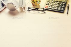 Office desk workplace by karandaev. Office desk workplace with coffee cup, notepad and headphones on wooden background with copy space. Sunny toned