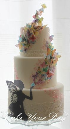 Cake Art: Three Tier Cream Cake with Lace and a Seated Black Fairy Blowing Cascading Multi-Colored Butterflies Up and Around The Cake   #CakeArt #Cakes
