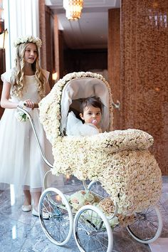 what a way to bring baby down the aisle! in a floral wedding carriage