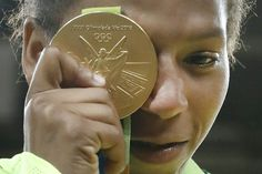 Brazil's Rafaela Silva celebrates with her gold medal following the women's -57kg judo contest of the Rio Olympic Games on August 8, 2016. Rafaela Silva, who grew up in Rio's notorious City of God slum, upset world number one Sumiya Dorjsuren to win the women's under-57kg judo, sparking pandemonium among fans. Silva sank to her knees in delight after a win that jump-starts Brazil's Olympic campaign and secures only their second medal after Felipe Wu's shooting silver.