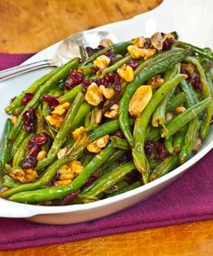 Roasted Green Beans with Cranberries!  Toss them with olive oil, salt, pepper,  and slivers of garlic. (recipe says sugar, too - but maybe honey instead?) Roast in a high heat oven for about 25 minutes until tender, browned in spots and just starting to shrivel. Add lemon zest, lemon juice, cranberries and walnuts.