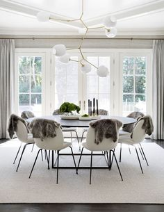 Stunning, Scandinavian dining room with large round table, white chairs, faux fur hung over the chairs, white French doors and abstract lighting | Tamara Magel Interiors