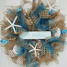 "22"" in Diameter Burlap and Teal Deco Mesh wreath accented with several types of ribbon (Teal, Tan, and White) along with three Starfish and 3 Sand-dollars. sign"