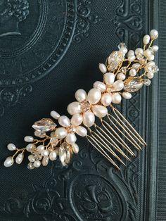 A pretty and simple wedding hair comb featuring ivory tone freshwater pearls, navette stones and shimmering crystals. Perfect for a simple hairstyle and also ideal for bridesmaids.  Available in gold or silver colour.  Approximate max length and width of detail: 11cm x 2.5cm.  Complete with keepsake box to treasure forever.