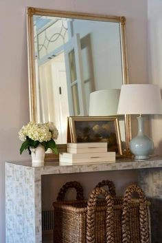Chic foyer with large woven basket tucked under stone waterfall console table filled with silver ...
