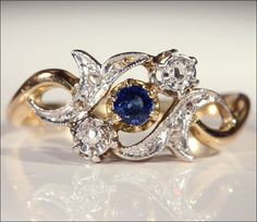 French sapphire and diamond ring. This one contains one round faceted sapphire of about .2 carats in a fabulous rich, deep blue surrounded by 8 rose cut diamonds. The ring is hand crafted of 18 karat gold and platinum and is marked with the French eagles head mark. Made in France around 1905, it shows off Art Nouveau lines with it's stylized leaf form.