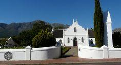 De 'Franschhoek Wine Tram' gaat richting de wijnvelden die elk tot een landgoed met wijnhuis behoren. Waar je ook uitstapt, achter elke oprijlaan ligt een landhuis te wachten waar je aan tafel kunt schuiven om je neus in een glas wijn te hangen. Photo: Franschhoek Wine Estate, South Africa