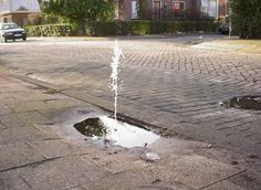 Helmut Smits - A fountain made by placing a small water pump in an existing pot-hole on the road. When it rains, small fountains appear. (From Beautiful Decay)