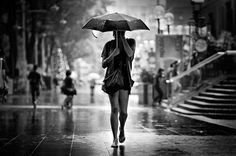 Lady with umbrella walking down the street.