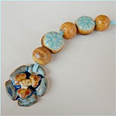 This set consists of a porcelain pendant and five beads.…