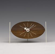 Lot 101: George Nelson. Watermelon table clock, model 2219. 1954, walnut, enameled metal. 8 w x 4 d x 4¾ h in. result: $4,600. estimate: $2,500–3,500. Walnut body with inlaid hour markers supported on three legs. Signed with Howard Miller decal label.