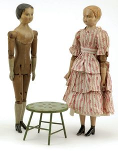 Pair of Joel Ellis Dolls - Springfield, Vermont, ca, 1870, wood mortise and tenon jointed dolls with pewter limbs, the first has painted blonde hair and wears period pink cotton dress, the second has black painted hair, no clothing, lot includes green painted decorated table