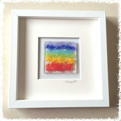 """Glass Fused Wall Art - Rainbow / Shakra Colours. SimplyP Glass Studio design and make a range of glass fused wall art in Dublin, Ireland. Glass Pictures This item is made by hand and contains layers of glass and frit which is tack fused in a glass kiln. You can touch and feel the object. The glass picture is 3""""x3"""" and frame is 8""""x8"""" Each glass picture is unique and may differ slightly."""
