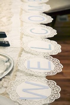 Use paper doilies to make a banner for tea party baby shower with baby's name