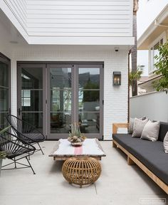 Modern, organic outdoor seating area with acapulco chairs and sofa with wood, rattan, and black and white accents. House Design, House, Home, Pretty House, Beach House Interior, Eclectic Home, Amber Interiors, Amber Interiors Design, Outdoor Seating Areas