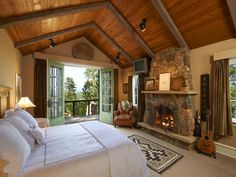 Master bedroom ideas~ i'd tone down the honky country decor but i like the wood ceiling, beams & fireplace