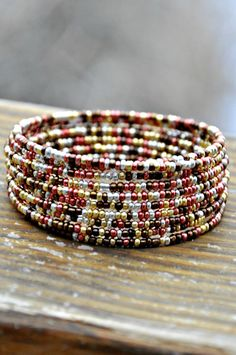 This beauty is made of gold, silver, bronze and copper/rosey toned micro seed beads strung on gold toned memory wire. MEMBER - Hole In Her Stocking