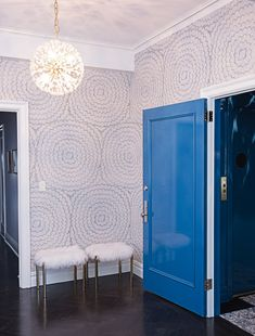 Beautiful entryway with glossy blue door, subtle design wallpaper and statement hanging light   Rebecca Soskin Design