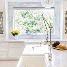 In this bright and airy kitchen space, a Waterstone Gantry faucet takes pride of place.