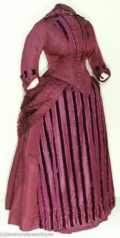 1880s - the center panel of the skirt is in a contrasting material to the bodice and rest of the skirt, an alternative to the swagged aprons in the mid-1880s.