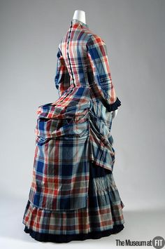 "Dress   Medium: Multicolor plaid cotton Date: c.1880 Country: USA Credit: Museum Purchase This two-piece dress features the plaid fabric known as ""madras"" which originated in the Indian town of Madras, on the Bay of Bengal. Like other Indian printed cottons, it was widely imitated in the West. Object Number: P92.21.1"