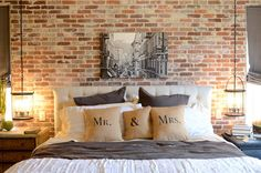 Love the pillows, brick wall, hanging lanterns and roman shades!!