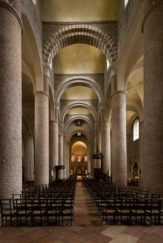 The Basilica of St. Philibert in Tournus, France, has a long nave lined with large columns on either side and topped with barrel vaults, features of the Romanesque period.