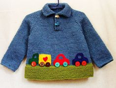This sweater will fit babies and toddlers 12 to 18 months old.    Hand knitted from denim blue and soft green 100% wool yarn, this polo neck pullover features car buttons, as well as appliqued truck and cars in bright primary colored felt. Would make a wonderful and unique shower or birthday gift!    Hand wash, lay flat to dry.    Sweater measures approximately 13 high, 12 across chest and 13 from neckline to cuff.
