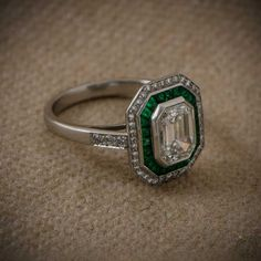 A Beautiful Emerald Cut Diamond Ring with a halo of Diamonds and a halo of emeralds and set in Platinum