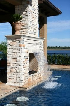 Outdoor fireplace with waterfall into pool. I would have the fireplace come further out into the pool and have the waterfall pour from either side of it instead of in front of it. Outdoor Spaces, Outdoor Living, Outdoor Decor, Porches, Future House, My House, Living Pool, Swimming Pool Landscaping, Landscaping Ideas