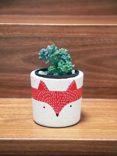 Handmade white concrete pot/planter with a friendly fox painted around it. Great as a pot for succulents or cactus, or even storing things like pens. The pot itself has been hand sanded and sealed, and comes without a drainage hole at the bottom.  Size wise, the pot is roughly 10cm high, 10cm wide at the top and tapers slightly to 9.5cm at the bottom. As this is a hand made product, your own pot will look slightly different to the one pictured and may have variations in both texture and...
