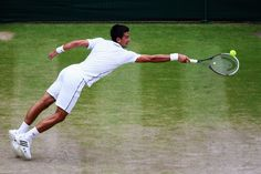 Novak Djokovic of Serbia at full stretch as he tries to make a return during the Gentlemen's Singles Final match against Roger Federer of Switzerland on day thirteen of the Wimbledon Lawn Tennis Championships at the All England Lawn Tennis and Croquet Club on July 6, 2014 in London, England. (Photo by Clive Brunskill/Getty Images)