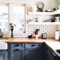 Open shelving, butcher block countertops and painted cabinets