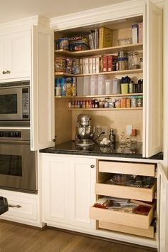 This dedicated baking center is nicely hidden away by a pair of bi-fold doors. Shallow shelves wrap three sides and keep ingredients handy. Lower cabinet pull-out drawers house bowls and measuring cups.