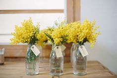 A clear bud vase filled with yellow mimosa and baby blue eucalyptus Baby Shower Yellow, Baby Shower Table, Baby Shower Flowers, Baby Yellow, Floral Baby Shower, Mellow Yellow, Pink Yellow, Yellow Centerpieces, Baby Shower Centerpieces