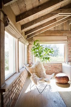 Wooden ceiling and light brick walls with ivory window treatments
