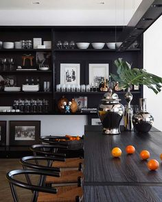 Black kitchen with open shelving in a home designed by Brazilian architect Guilherme Torres