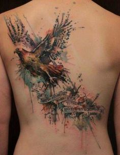 A bird of prey flies away from a banner with a powerful phrase in this watercolor tattoos by Gene Coffey