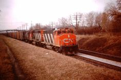 CN east bound train #392 climbing the grade out of Toronto toward Kennedy Rd., Scarboro, on April 4, 1976.  Power is GP38-2 5567, GP40-2L(W) 9421 and MLW C-424 3220